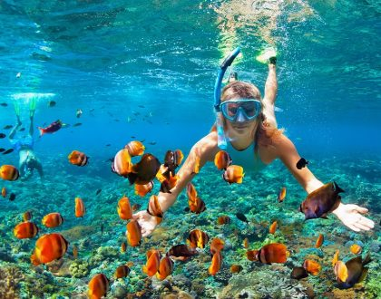 girl snorkeling with orange fish